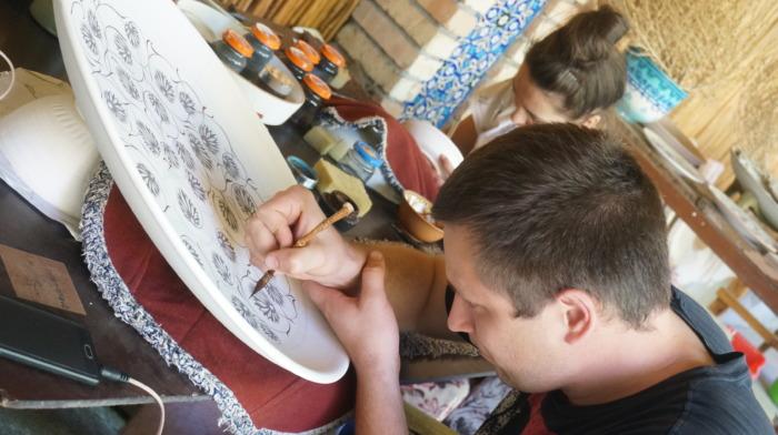 手描きのお皿を製作する男性