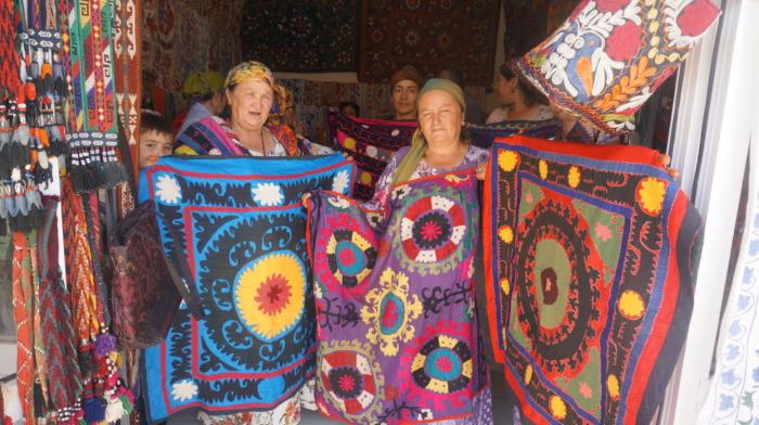 カラフルなスザニ刺繍を広げる女性たち