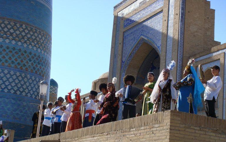 ヒヴァのイスラム建築の前で民族衣装を着て踊る人々