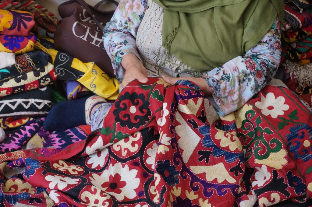 赤い生地に刺繍をする女性の姿